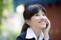 Donna d'affari cinese che parla al telefono e sorride per strada — Foto stock
