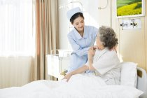 Chinese nurse giving shoulder massage to senior woman — Stock Photo