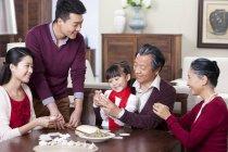 Cheerful multi-generation family making Chinese dumplings — Stock Photo