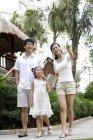 Pais chineses com a filha de pé e apontando a estância turística — Fotografia de Stock