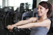 Chinese woman lifting dumbbell in gym — Stock Photo