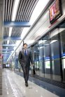 Chinese businessman with briefcase walking at subway station — Stock Photo