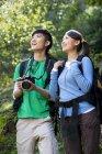 Китайские друзья с цифровой камерой на прогулке в лесу — стоковое фото
