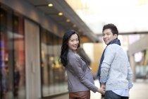 Casal chinês de mãos dadas na rua da cidade e olhando para trás, visão traseira — Fotografia de Stock