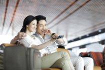 Coppia cinese guardando la fotocamera digitale nel salone dell'aeroporto — Foto stock