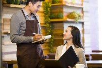 Garçon chinois prenant la commande de femme au restaurant — Photo de stock