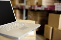 Laptop on cardboard box in warehouse — Stock Photo