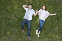 Draufsicht auf junge chinesische paar liegen auf dem Rasen — Stockfoto