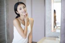 Mujer China aplicar Crema hidratante a la piel - foto de stock