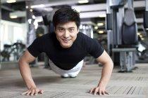 Chinois homme faire push ups à la salle de gym — Photo de stock