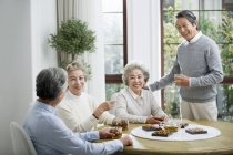 Senior Chinese friends relaxing and talking while tea party — Stock Photo