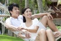 Chinese couple relaxing in hammock on vacation — Stock Photo