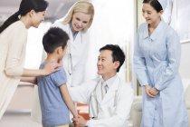 Chinesische Ärzte sprechen mit Junge im Krankenhaus — Stockfoto