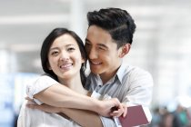 Chinese couple embracing at airport with tickets and passport — Stock Photo