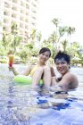 Chinese couple relaxing in hotel pool and looking in camera — Stock Photo