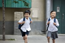 Chinese children running from school building — Stock Photo