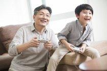 Китайський діда і онука, граючи відеоігор у вітальні — стокове фото