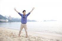 Китаец с протянутыми руками на пляже залива Репульс, Гонконг — стоковое фото