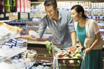 Chinese couple shopping in supermarket with cart — Stock Photo