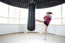Chinesische Frau treten Boxsack — Stockfoto