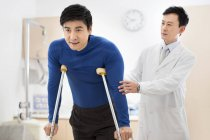 Chinese doctor helping patient with crutches — Stock Photo