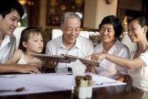 Chinesischen mehr-Generationen-Familie auf der Suche durch Menü im restaurant — Stockfoto