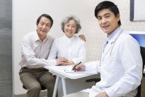 Chinese doctor sitting with senior couple in hospital — Stock Photo