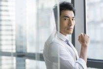 Nachdenklicher chinesischer Geschäftsmann steht im Büro hinter Glaswand — Stockfoto