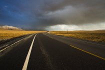 Highway under dramatic sky in Qinghai province — Stock Photo