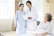 Chinesische medizinische Arbeiter mit Patienten im Krankenhaus — Stockfoto