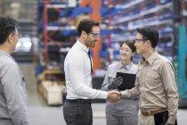Бизнесмен и инженер пожимают руку на заводе — стоковое фото