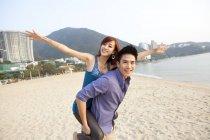 Chinese couple playing piggyback on beach of Repulse Bay, Hong Kong — Stock Photo