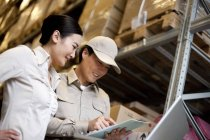 Chinese businesswoman in warehouse with workers using a laptop — Stock Photo