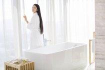 Chinesische Frau im Bademantel stehen durch die Fenster im Bad — Stockfoto