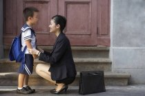 Chinese businesswoman crouching with schoolboy in front of door — Stock Photo