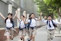 Niños en uniforme escolar corriendo en la acera - foto de stock