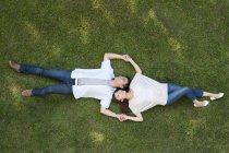 Вид зверху молода Китайська пара лежить на траві — стокове фото