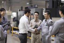Бизнесмен и команда инженеров пожимают руки на заводе — стоковое фото