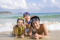 Молодая семья с подводное маски, лежа на пляже — стоковое фото