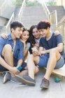 Chinesische Freunde betrachten Smartphone auf Treppen mit skateboards — Stockfoto