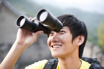 Chinese man using binoculars outdoors — Stock Photo