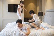 Китайские братья и сестры веселятся и играют с отцом в постели — стоковое фото