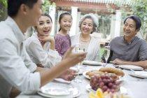 Familia China hablando en mesa de comedor en patio - foto de stock