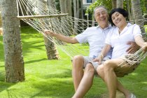 Senior Chinese couple relaxing in hammock on vacation — Stock Photo