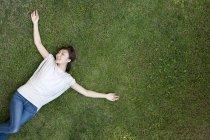 China joven tumbado en el césped con los brazos extendidos - foto de stock