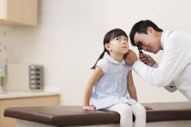 Chinese doctor examining girl ear — Stock Photo
