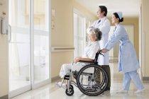 Chinesische Ärzte kümmern sich um Seniorin im Rollstuhl — Stockfoto