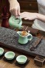 Закри жіночих рук розливати чай в чайник — стокове фото