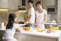 Chinese parents with daughter cooking in kitchen — Stock Photo