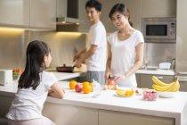Padres chinos con hija de cocción en cocina - foto de stock